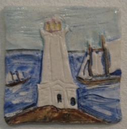 Louisbourgh lighthouse with tall ships in the harbour