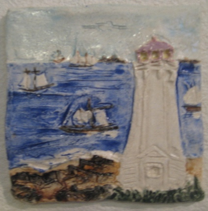 Louisbourg Lighthouse Wallhanging, with old lighthouse foundation in foreground, tall ships and the fortress in the background. 5.5 inches.